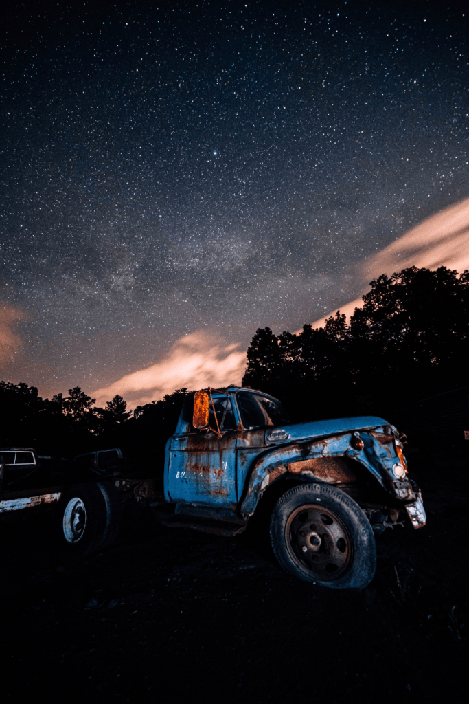 wrecked classic blue pickup truck near trees