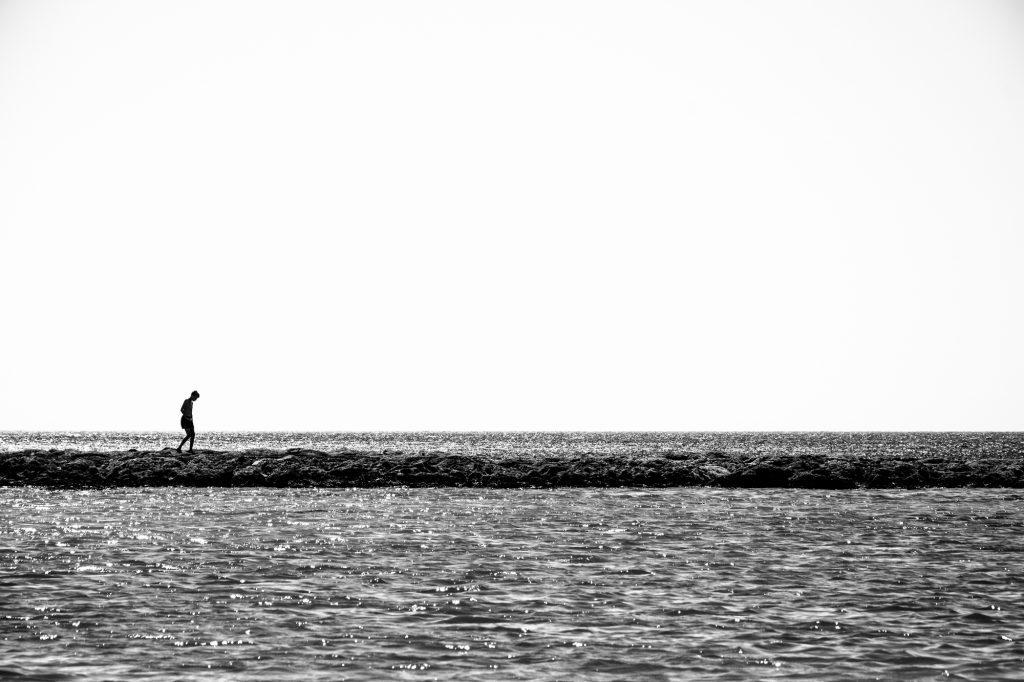 A child walks on a thin coastline. Minimalistic black and white photo